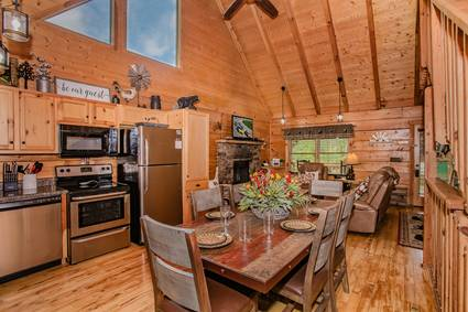 view of open concept living area, dining table for 6, L shaped kitchen with stainless steel appliances, living room in background with leather couch, armchair, stone fireplace, and flat screen tv