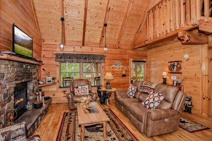 living area, high ceilings, stone fireplace, flat screen tv above, light brown leather couch and armchair with coffee table in front
