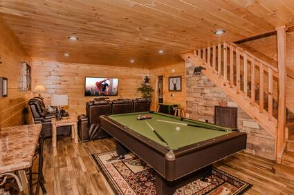 downstairs family room, dark brown and green pool table, tv space with a large flat screen and two large brown leather couches