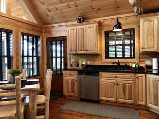 Kitchen with hardwood cabinets, granite counters and dining table