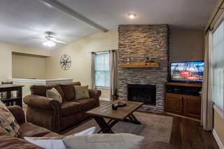 Living room area with sofa and loveseat, gas fireplace and large screen TV
