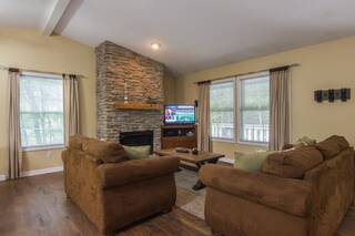 Wide view of living room with stone fireplace, flat screen TV