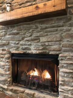 Stone gas fireplace with flames.  Available Oct. 1 to March 31.
