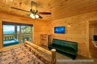 King suite in A View For All Seasons cabin near Gatlinburg with full-size futon couch and tv