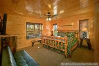 Relaxing king bedroom with flat-screen tv and full-size futon at A Grand View Lodge cabin in Pigeon Forge