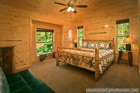 Large king-size bedroom with wooded view and full-size futon at Pigeon Forge cabin Grand View Lodge