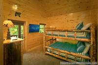 Double queen bunk bed room with tv in Pigeon Forge cabin with wooded view