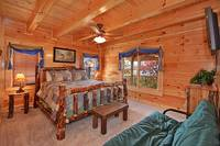 Large queen-sized bedroom with futon in Morning View Manor cabin in Pigeon Forge