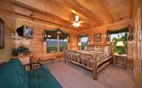 King-size bedroom with tv and full-size futon in Majestic View Lodge cabin in Pigeon Forge