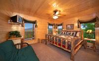 King-size bedroom that overlooks the mountains with tv and full-size futon couch in Majestic View Lodge cabin in Pigeon Forge