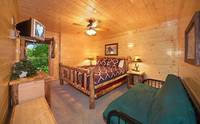 King-size bedroom with tv and full-size futon couch in Majestic View Lodge cabin in Pigeon Forge