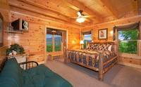 King-size bedroom that overlooks the mountains with full-size futon couch in Majestic View Lodge cabin in Pigeon Forge
