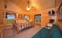 King-size bedroom that overlooks the mountains with tv in Majestic View Lodge cabin in Pigeon Forge