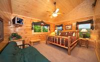 King-size bedroom with full-size futon couch in Majestic View Lodge cabin in Pigeon Forge