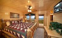 Master suite in Cades Cove Castle 8 bedroom cabin in Pigeon Forge with deck