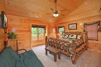 King-size bedroom with full-size futon and private tv at Dream View Manor cabin in Pigeon Forge