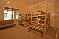 Bedroom at The Big Moose Lodge with two sets of queen bunk beds and a full-size futon