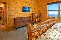 Spacious bedroom with full-sized futon bed and flat-screen tv at Majestic View Lodge