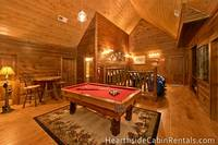 Large entertainment area inside an 8 bedroom cabin in Pigeon Forge with pool table and home theater system.