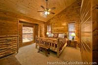 King-size bedroom inside Pigeon Forge cabin with rustic furniture.