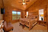 King-size suite inside 8 bedroom Pigeon Forge cabin with wooden furniture, rustic decor and mountain views.