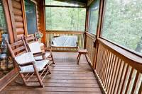 Wooden rocking chairs and porch swing