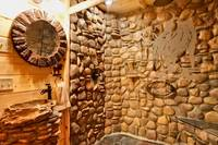 "Elegant bathroom in the ""Wolf Room"" with a large rock shower and glass doors"
