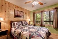 Across the Smokies - bed and view in the room of this 3 bedroom Gatlinburg cabin rental