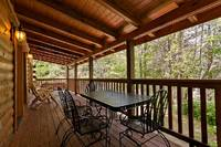 Across the Smokies - outdoor porch with chairs and table of this 3 bedroom Gatlinburg cabin rental