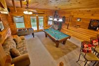 Game Area of Smoky Trails with pool table, foosball, dartboard and sleeper sofa