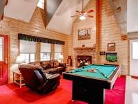 Living room with furniture, fireplace, TV and a pool table