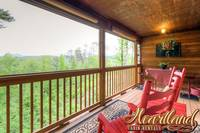 Wooden rocking chairs on the deck with views of the mountains