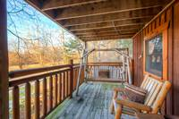 Enjoy the wooden porch swing and chairs on the porch of this 2 bedroom cabin in Pigeon Forge