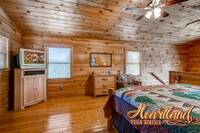 Master bedroom with TV and jacuzzi upstairs of this Pet Friendly Cabin