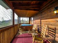 Hot tub and rocking chairs on the screened in porch