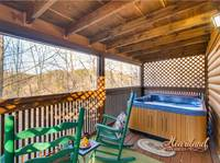 Hot tub and rocking chairs on the deck outside of the master bedroom