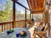 Back deck area with gas grill and wooden rocking chairs