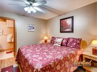 Bedroom with king sized bed and ceiling fan