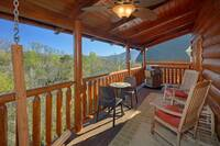 Gas grill, table and chairs and rocking chairs on the back deck of this affordable cabin near Pigeon Forge