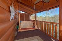 Enjoy a cup of morning coffee in the wooden porch swing