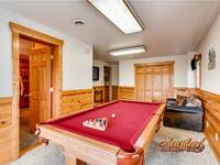 Full size pool table in this room with a flat screen TV and seating