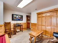 Flat screen TV with wooden rocking chair near the pool table