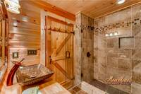 Custom tiled shower with a rain and massage shower head as well as a waterfall vanity sink for the ultimate in luxury