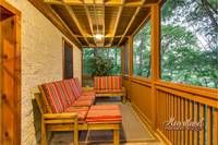 Screened-in deck with a sunken hot tub as well as an outdoor tv and rocking chairs