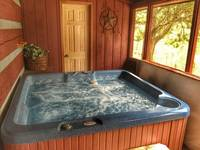 Hot tub located in screen, covered porch