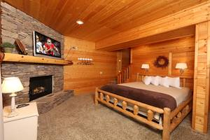 Downstairs Bedroom with King Bed, Electric Fireplace, and Jacuzzi Tub