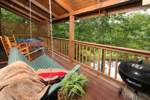 Back Deck with Hot Tub, Bench Swing, Charcoal Grill, and Rocking Chairs Overlooking Pond