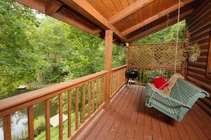 Bench Swing on Deck Overlooking Pond