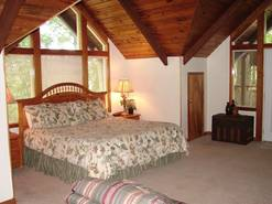 master bedroom with king bed and tv with private bath and electric fireplace and deck with hot tub