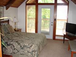br #2 with queen bed tv and deck with chairs and view at When Pigs Fly in Gatlinburg TN